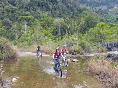Cycling tourists crossing the shallow stream in countryside of Kuching