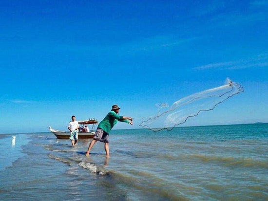 Fisherman releasing a net into the sea
