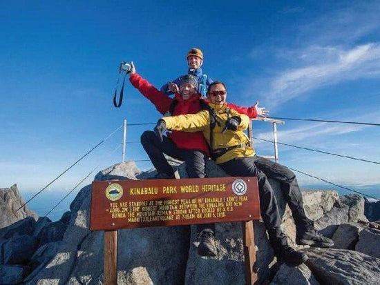Hikers posing to a photo at the top of Mount Kinabalu