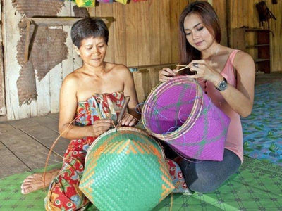 Iban natives in Batang Ai teaching tourists basket weaving