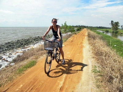 Lady cycling next to the ocean in Kerian