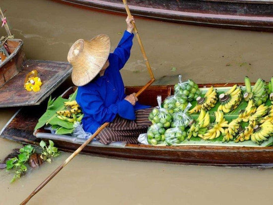 Lady selling fresh fruits on her boat at Damnoen Saduak Floating Market