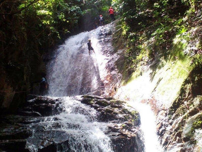 Man abseiling down a big waterfall in Gopeng