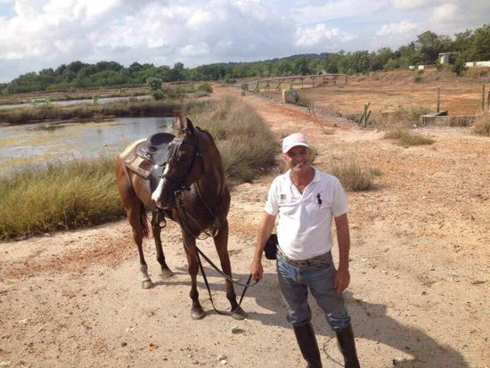 Man holding a rope onto horse at Pasir Gudang