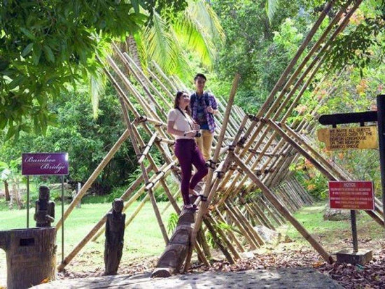 Tourists standing on a bamboo structure at Sarawak Cultural Village