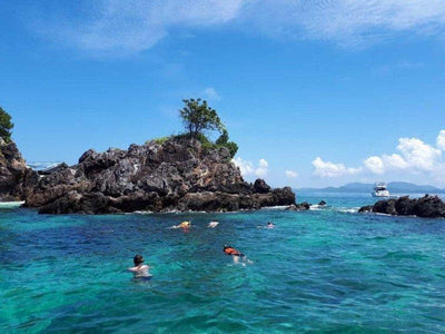 Tourists swimming and snorkelling near the rocks by the beach at Koh Samui