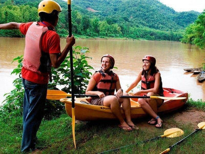 Trainer briefing tourists on kayak by the river in Laos