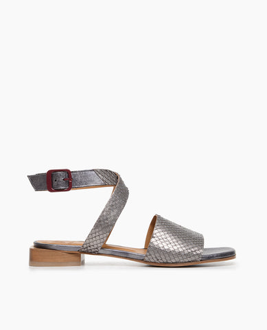 Coclico women's flat ankle strap sandal in a pewter snake embossed leather with a a red buckle. Coclico shoes are sustainably made in Spain.