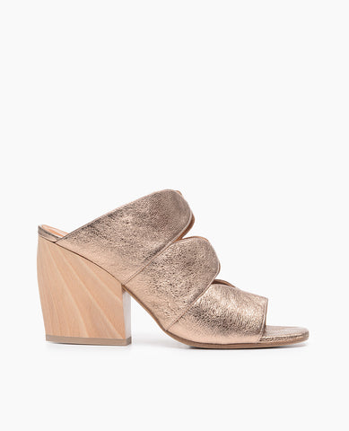 Coclico women's glamorous yet classic slide with metallic blush leather upper and a sculpted wood heel. Coclico shoes are sustainably made in Spain.