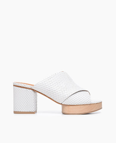 Coclico women's bold cross-strap slide with a wood platform and leather wrapped heel. Coclico shoes are sustainably made in Spain.