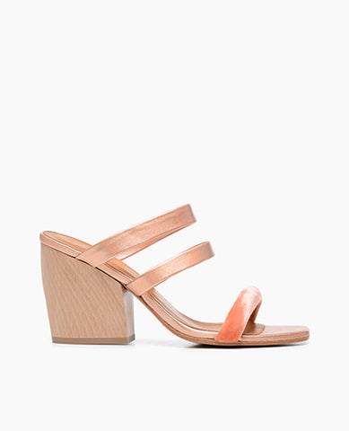 Coclico women's exquisitely contemporary slide that mixes luxurious melon hued silk velvet with iridescent peach metallic leather on a sculpted wood heel. Coclico shoes are sustainably made in Spain.
