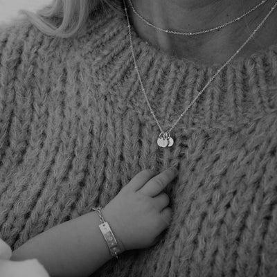 A mother wears a sterling silver keepsake necklace with small disc pendants, each with a letter of her children's names.  Her daughter is in her arms and wears a sterling silver bracelet.