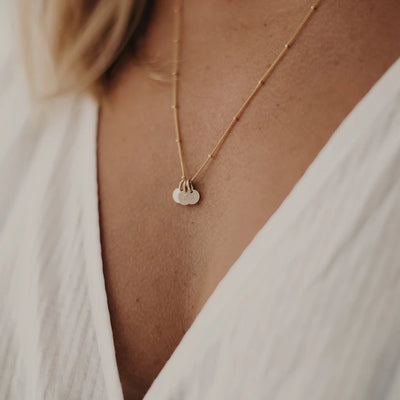 A woman is wearing a personalised initial necklace and the pendants are made from solid gold and have personalised hand-stamped letters on them.