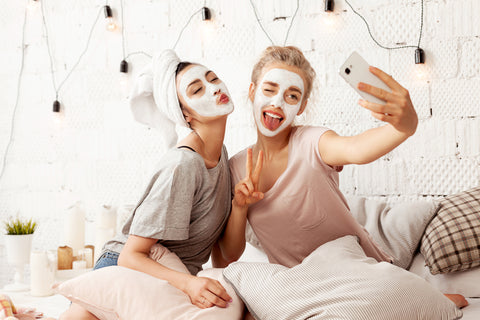 friends sharing an at home facial taking a selfie girls night in