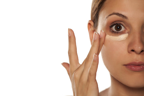 woman applying natural makeup concealer under eyes raw beauty minerals