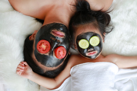 mother and young daughter enjoying a charcoal mask together