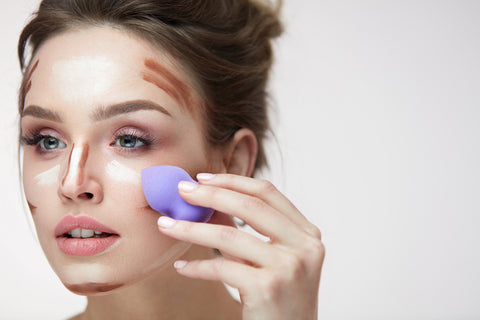 girl blending makeup with a beauty sponge raw beauty minerals