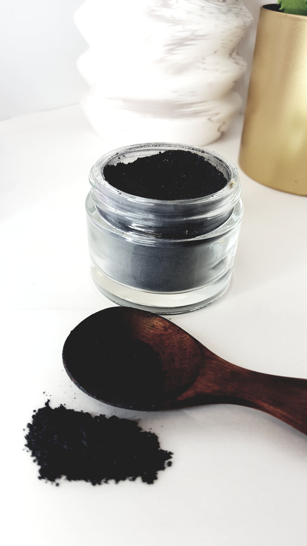 activated charcoal scrub in glass jar with wooden spoon