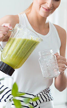 Woman Pouring Greens First Smoothie into Glass Cup