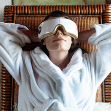 Woman relaxes wearing eye and temple massager