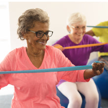 Older Woman with Glasses Using Resistance Bands