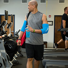 Freeze Sleeve Cold Therapy Compression Sleeve - man walking out of gym