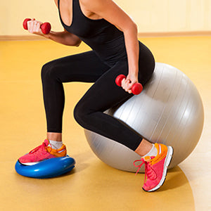BodySport Balance Disc Pro - woman working out on disc sitting on ball