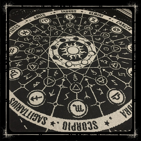 Black and bone zodiac and stars blanket spread across a bed