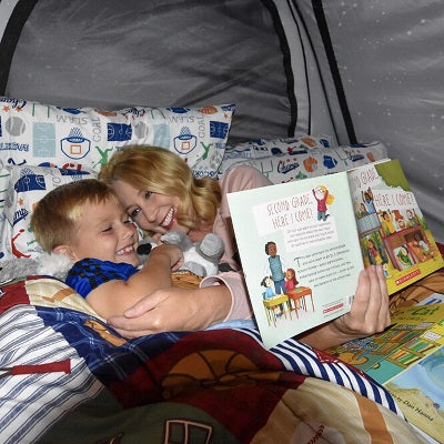 Mom and son reading book snuggled in bed