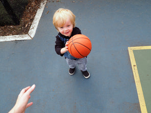 Point of view playing basketball with a young blond boy