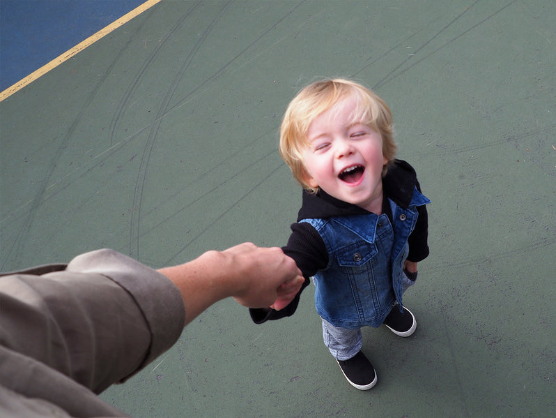 Holding a young boy's hand on a basketball court.