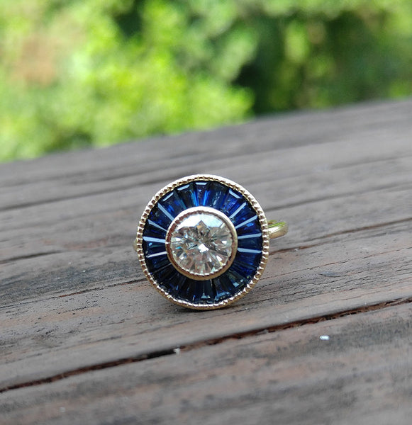 Moissanite - 1ct, 6.5mm  Moissanite Set in a 14K Yellow Gold and Baguette Blue Sapphire Halo - In The IceBox