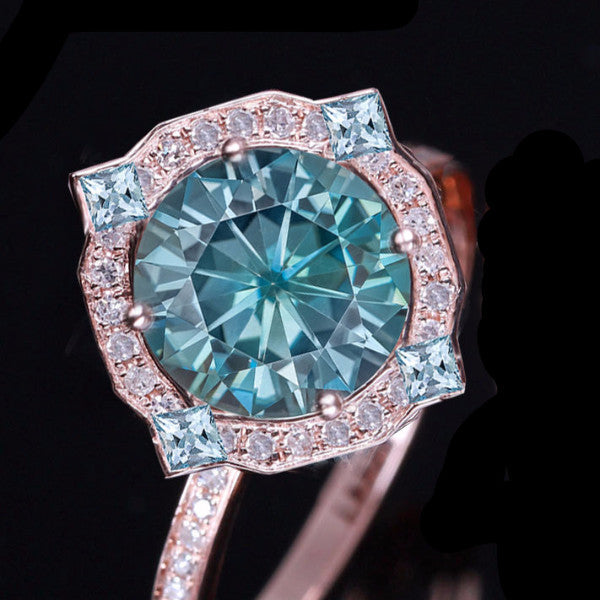 Moissanite - Caribbean Blue 2ct. 8mm Blue Round Brilliant set in an 14k Rose Gold Diamond and Aquamarine Halo Setting