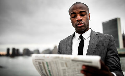 Black man reading newspaper