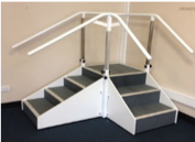 Corner exercise stairs with height adjustable hand rails at InterAktiv health