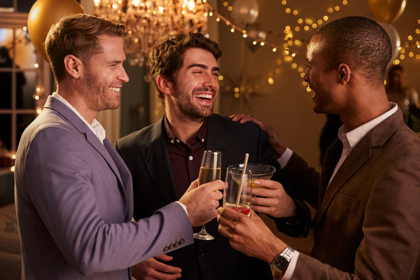 Male friend in different suit styles celebrate a toast at a party