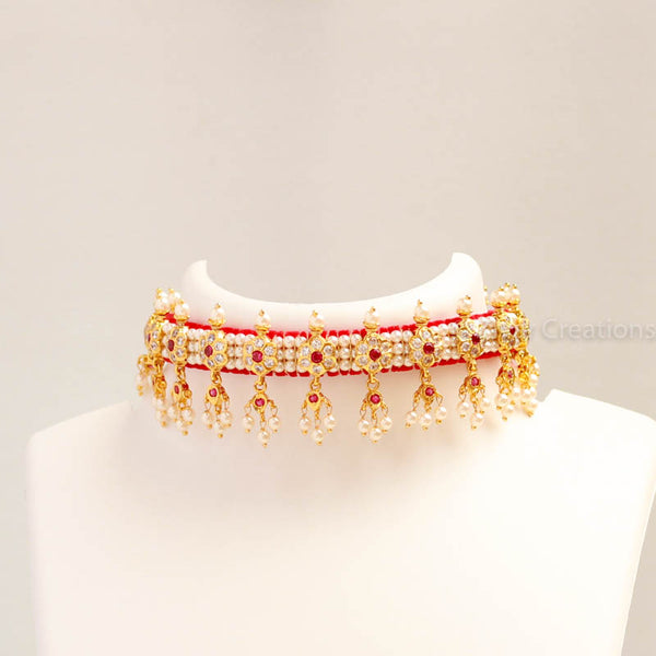 Beautiful chocker is embedded flower shape with white - pink colour stones and made from golden finish metal. This necklace is woven with good quality pearl beads and comes with adjustable thread so that you can fit it properly. It goes match with all type of ethnic sarees and dresses. It paired with matching earrings.