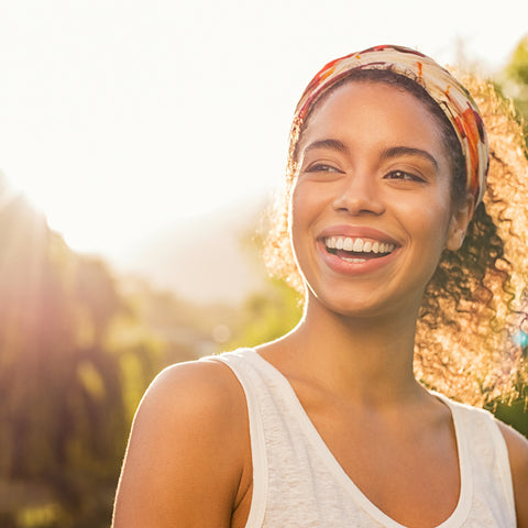 image of a girl with curly hair smiling on a sunny day