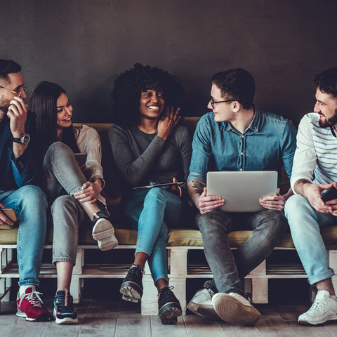 image of a group of young people sitting on a bench and working together