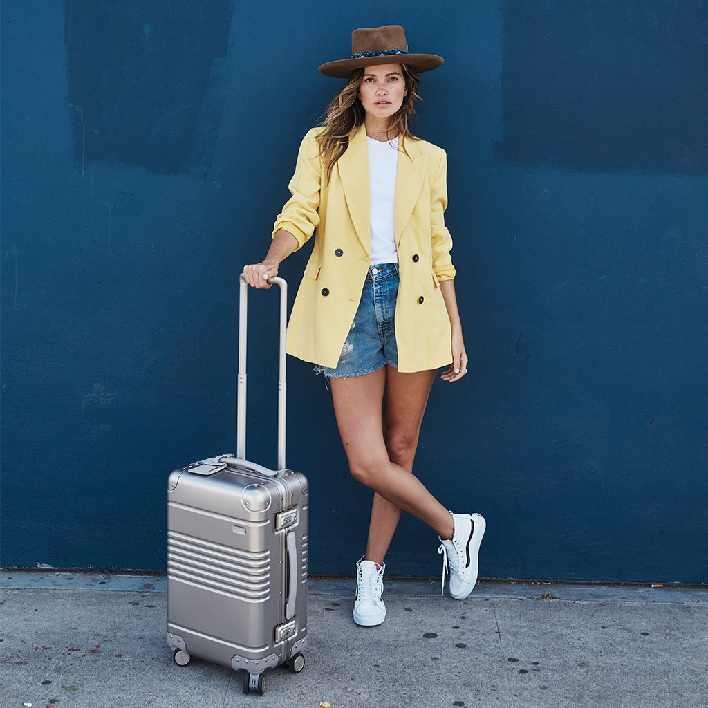 Model posing on the street with her frame carry-on in champagne aluminum edition.