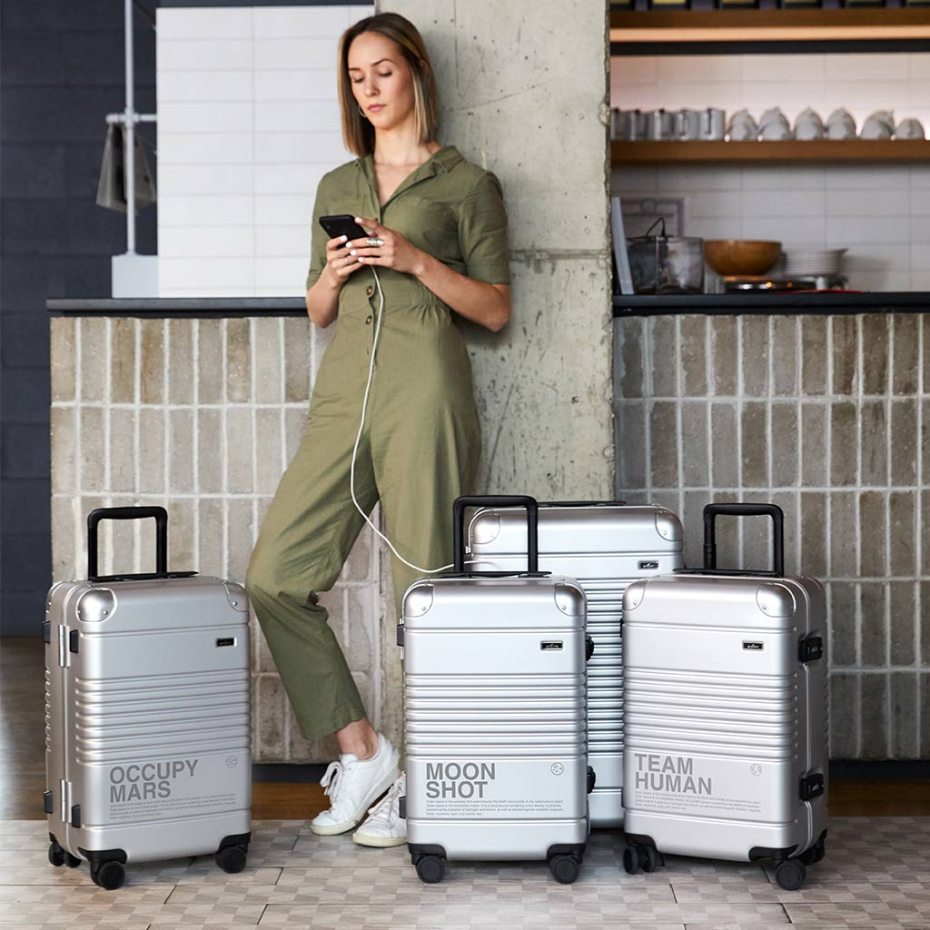 Woman charging her phone while traveling with the Arlo Skye Space Edition Collection.