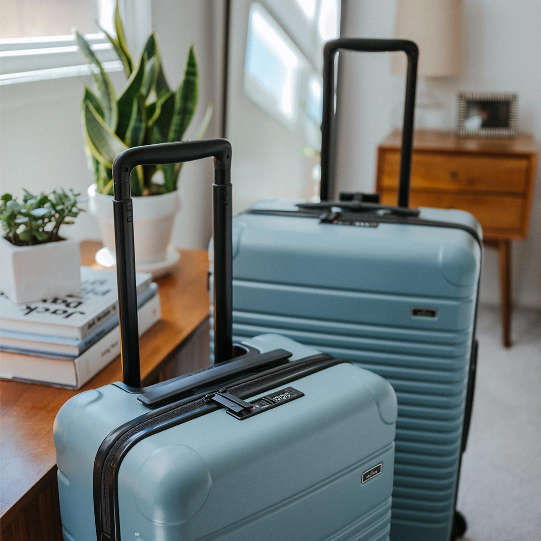 The Arlo Skye Zipper Carry-On Max and Zipper Check-In in Sea Sage. Both bags are standing in the bedroom.