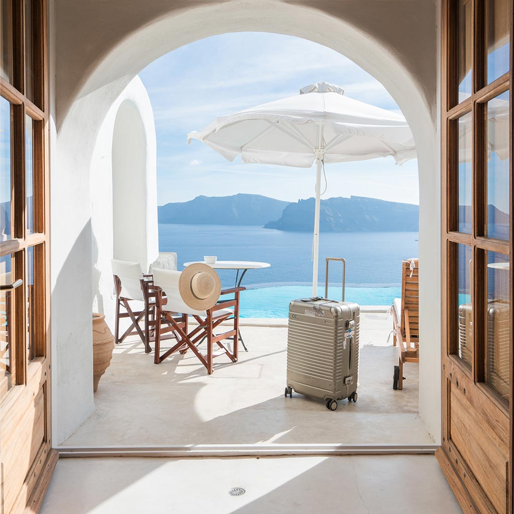 A hotel room in Greece with the Arlo Skye Check-In in Champagne Coloway visible in the balcony with water behind.