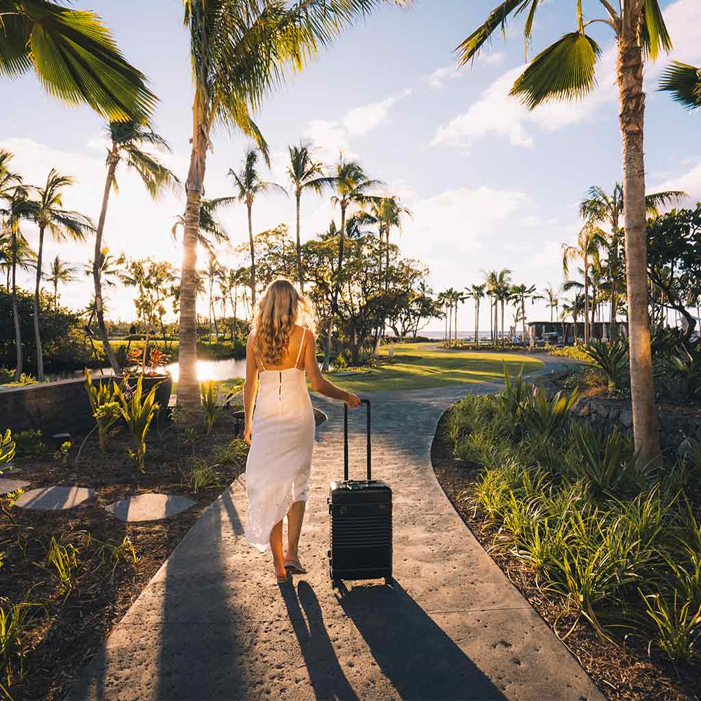 A girl in white dress with black Arlo Skye Frame Carry-On Max walking down a pathway in a lush tropical garden.