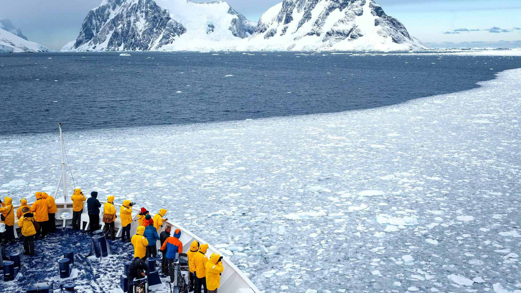 View of Icebergs in Antarctica with people watching the view from cruise ship.