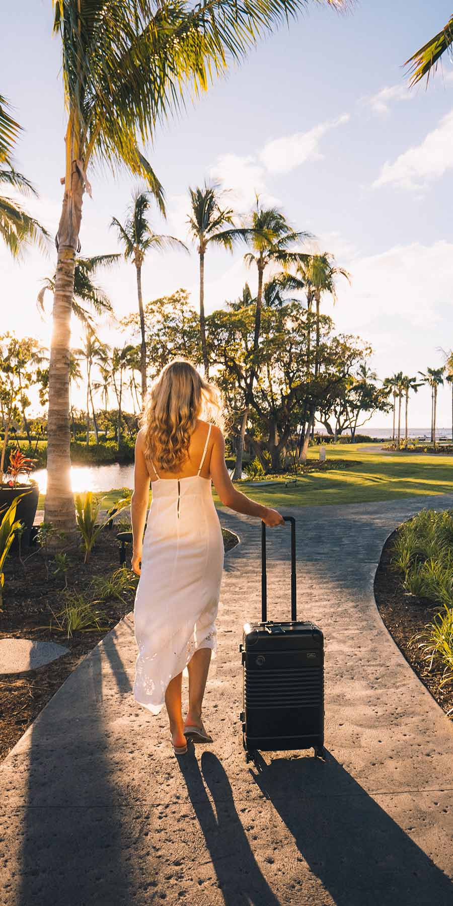 Woman rolling her black carry-on down a pathway surrounded by trees at a hotel in  Hawaii.