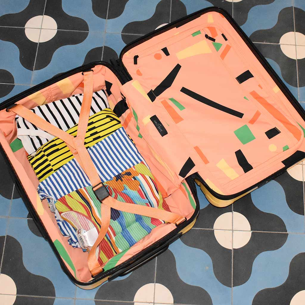 An open Arlo Skye x Dusen Dusen carry-on that is laying on the ground featuring a vibrant lining print designed by Dusen Dusen with some clothes neatly packed.