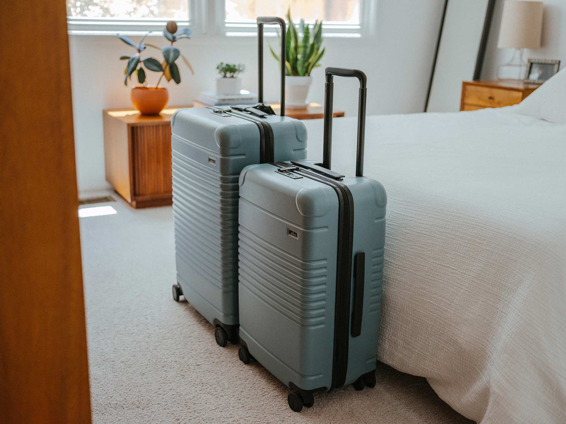 Arlo Skye luggage in sea sage colorway in a room.