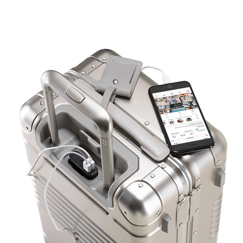 Top down view of frame carry-on in champagne aluminum edition with the spare charger in use