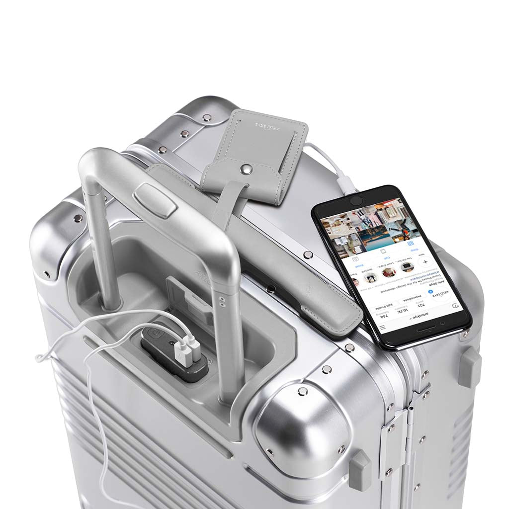 Top down view of frame carry-on in silver aluminum edition with the spare charger in use